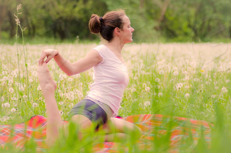 woman wearing a white tank top doing yoga positions in the middle of field photo