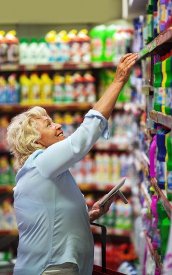 Smiling senior woman with pad and shopping basket taking household chemicals from the upper shelf in the store photo