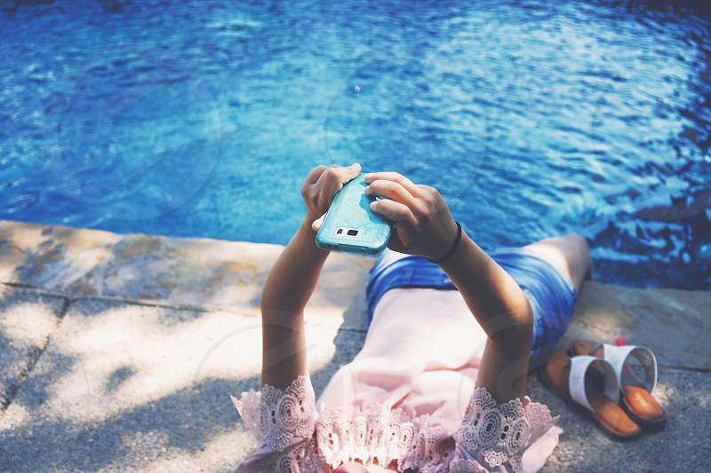 Woman poolside during summer checking phone. photo