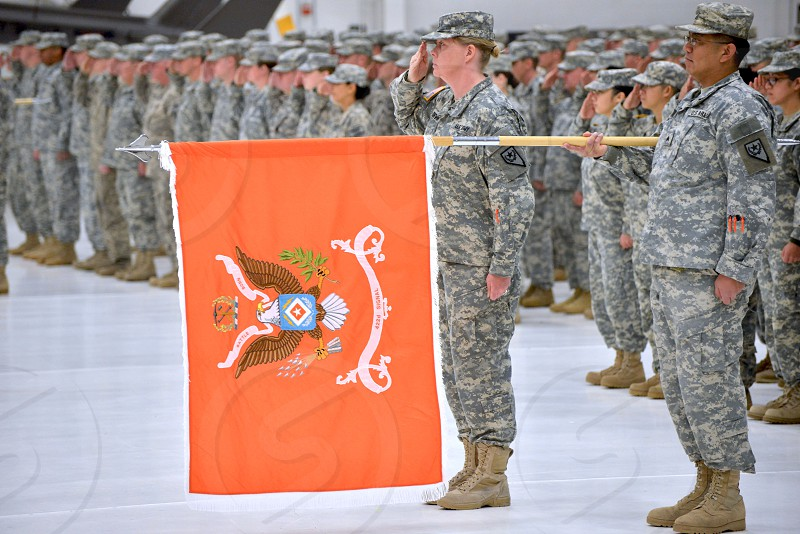 armed forces wearing gray and white camouflage uniforms standing in line with one person holding orange flag during daytime photo