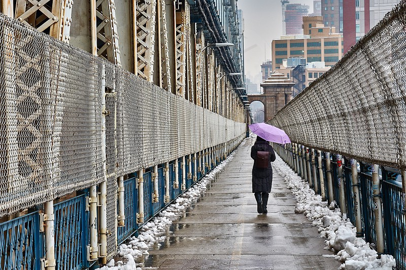 woman in brown dress walking on an alley using a purple umbrella during daytime photo