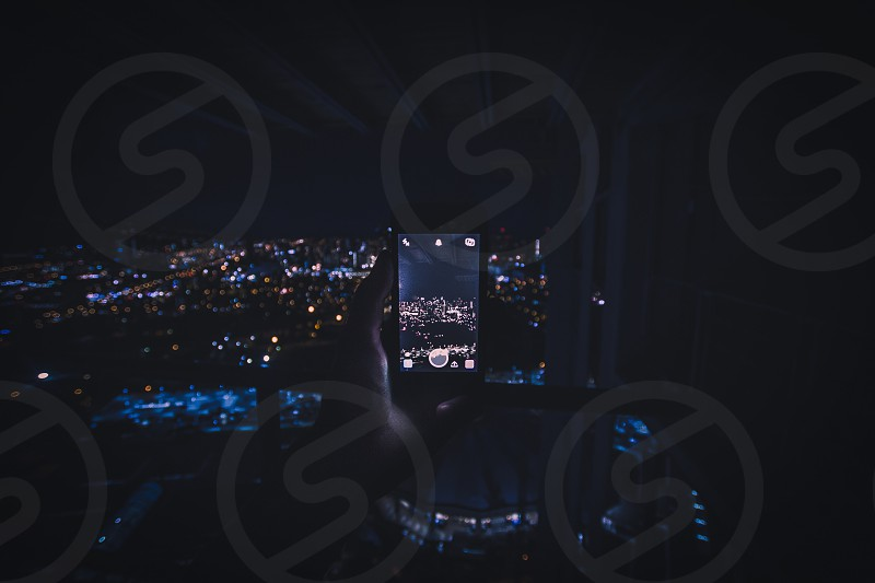 person holding smartphone taking photo of city landscape at night with lights photo