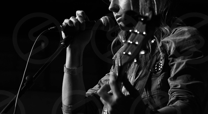 grayscale photo of person holding microphone and guitar photo