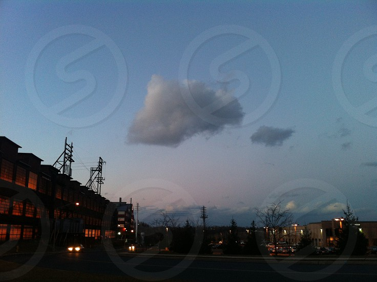 white small cloud and large cloud over mid rise buildings photo