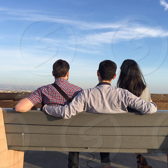 2 man and woman sitting on gray wooden bench photo