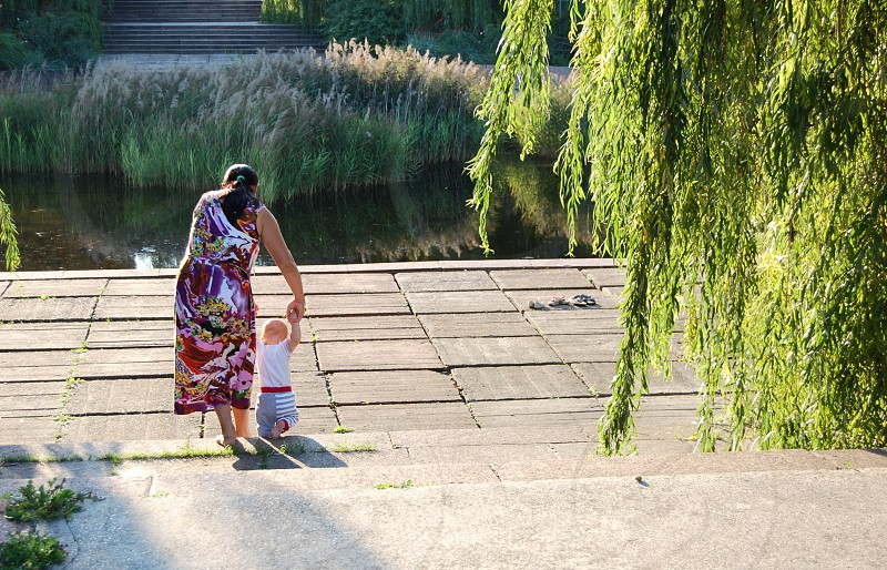 A young mother teaches her little child to walk on a sunny day in the park barefoot photo