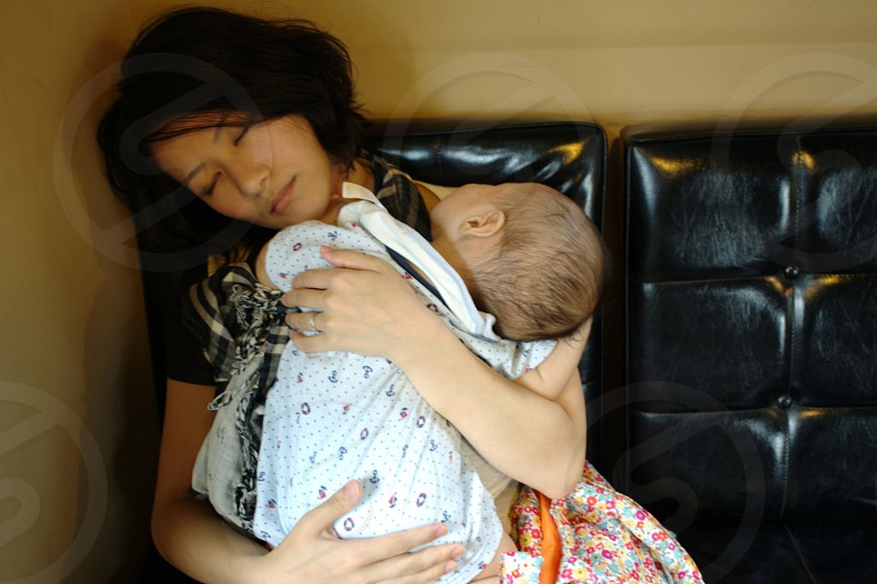 woman holding baby in white carrier white sleeping sitting on black chair photo