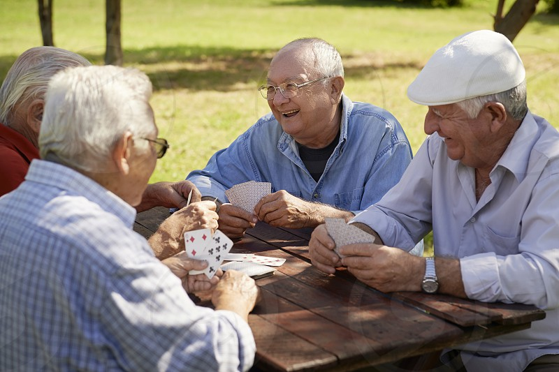 game; playing; cards; old; people; senior; laughing; 60s; 70s; active; aged; bench; buddies; caucasian; cheerful; closeup; elderly; enjoy; four; free time; friends; fun; glad; grandfather; group; happiness; happy; hispanic; hospice; joy; latino; lifestyle; male; man; mates; men; natural; park; pensioner; persons; relaxing; retired; retirement; seniors; sitting; smiling; talking; together; white photo