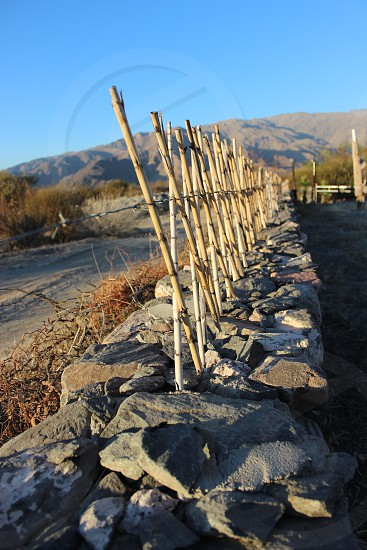 stone fence with barbed wire and rods as a defense to theft photo