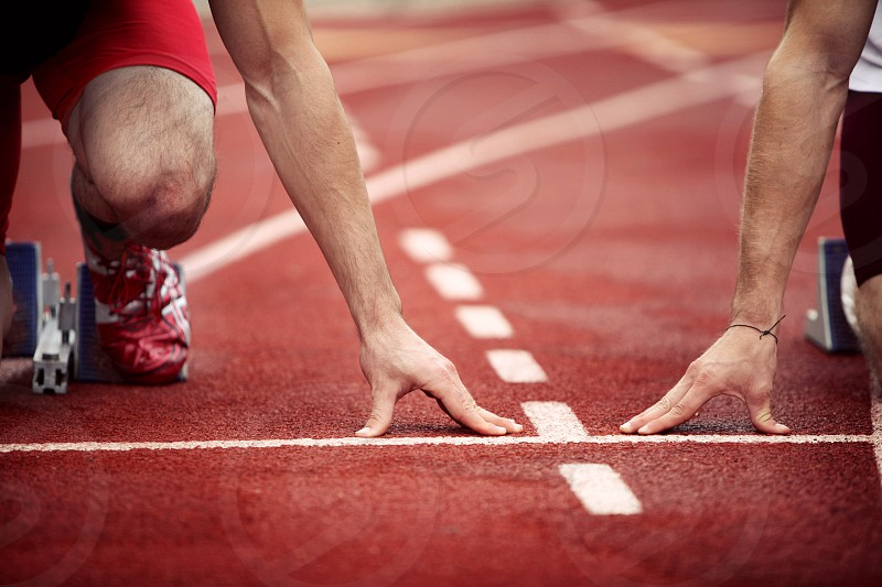 Runners feeling the pressure as they kneel at the starting blocks.  Race track lines hands fingertips shoes running sports athletics shorts fitness shape red shoes reminder rivals excitement anticipation marks photo