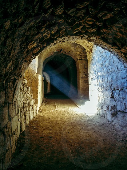 beige stone arch passage with sun rays photo