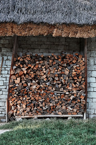 Logs of firewood stored under the stone shed. Stacked firewood in a backyard back of house photo