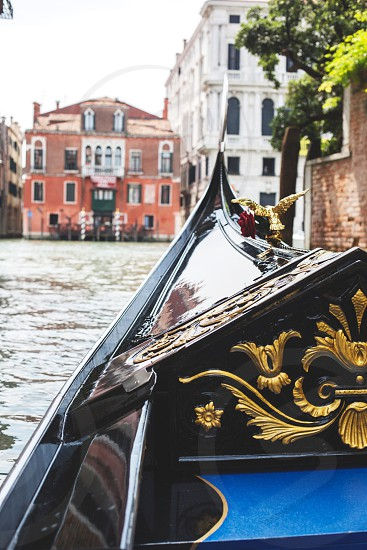 black gondola with gold accent on canal photo
