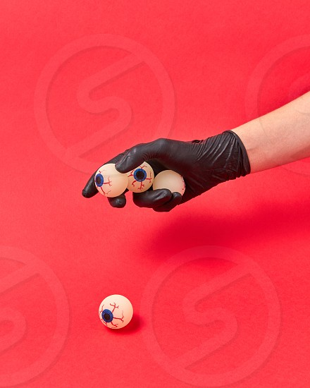 Woman hand in a black glove holds human eyeballs on a red background copy space. Halloween simbol. photo