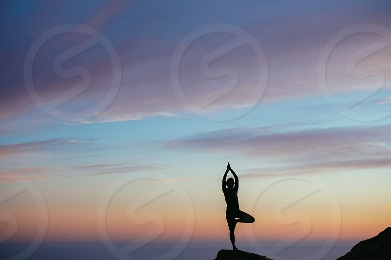 silhouette of a person doing yoga during golden hour photo