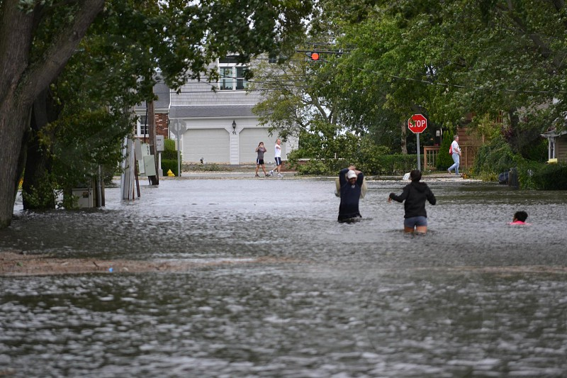 people walking on a flooded street photo