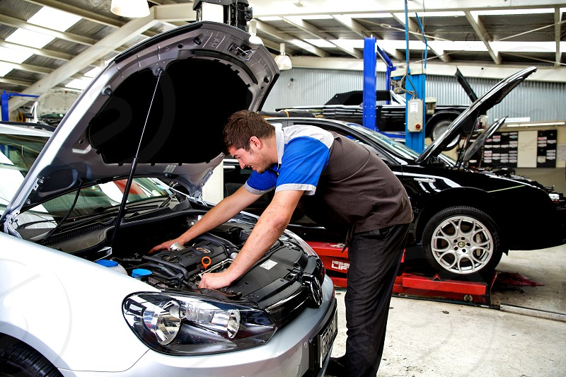 Mechanic looks into new cars engine bay photo