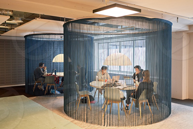 Students sit at tables surrounded by thread curtains in the university of amsterdam. photo