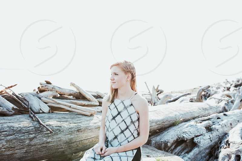 woman in white black checkered dress sitting on tree logs photo