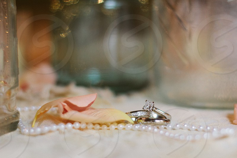 silver ring beside white pearl necklace  photo