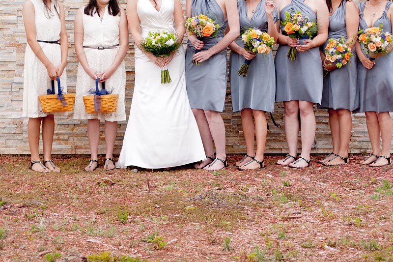 bride with bridesmaid standing near wall photo