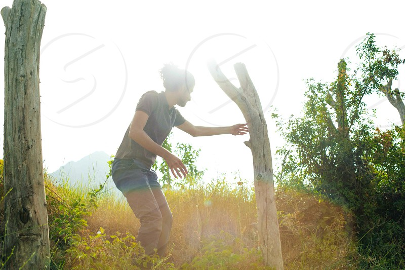 man holding dead tree bark photo