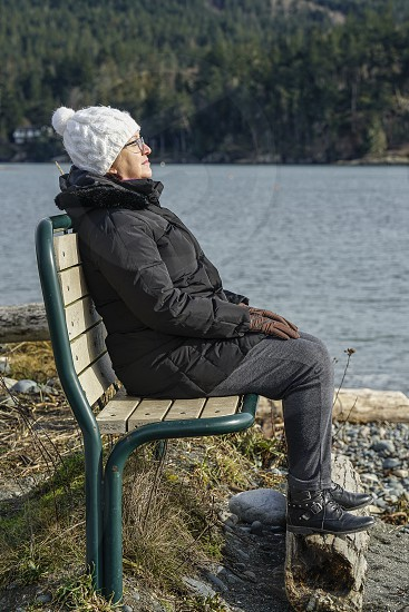 A woman absorbing the suns rays on a cool winter's day. photo