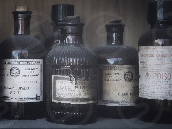 white labeled poison and oil bottles on shelf photo