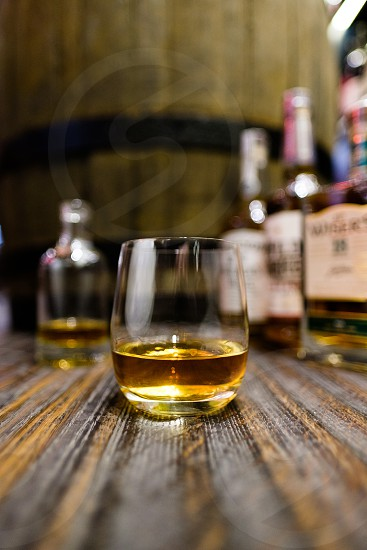 Glass of whisky on a wooden surface with other whisky bottles behind it in a shop environment with a whisky barrel  photo