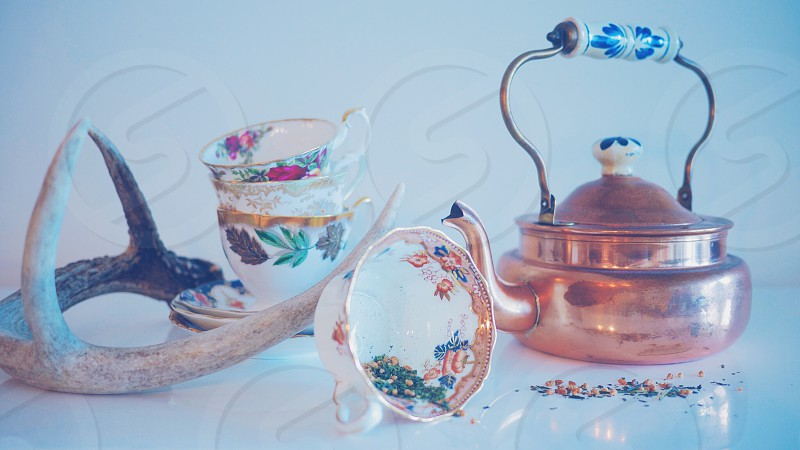 Vintage/antique teacups saucers and copper tea kettle photo