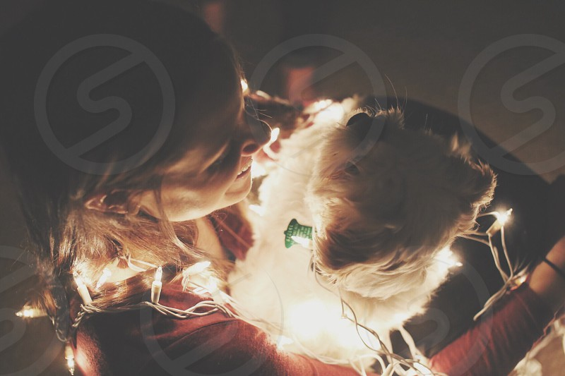 woman hugging her white terrier with string lights photo