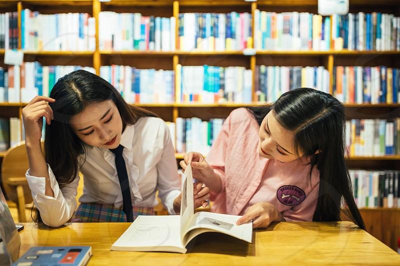 Environmental portrait bookstore books two Asia girl photo