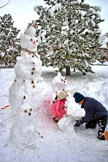 Father and daughter build a family of snowmen. photo