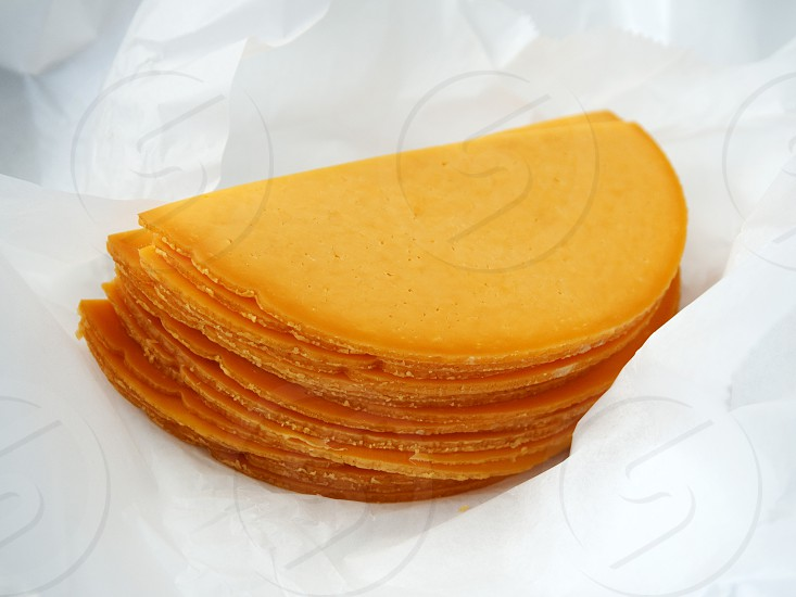 Cut smoked cheddar cheese on wax paper photo