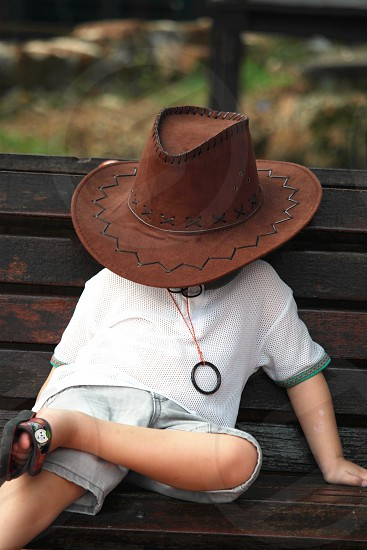child sitting in black wooden bench wearing brown cowboy hat and white sleeved crew neck shirt during daytime photo