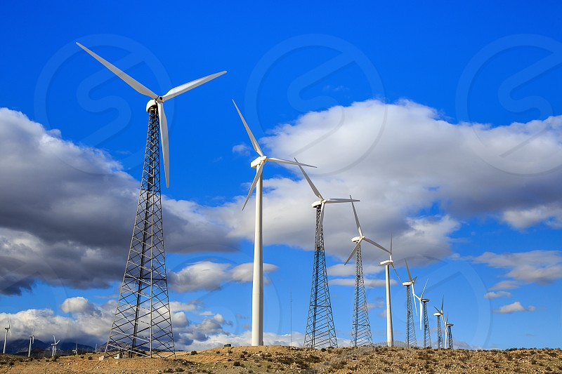 wind turbines on brown ground under white clouds and blue sky during daytime photo