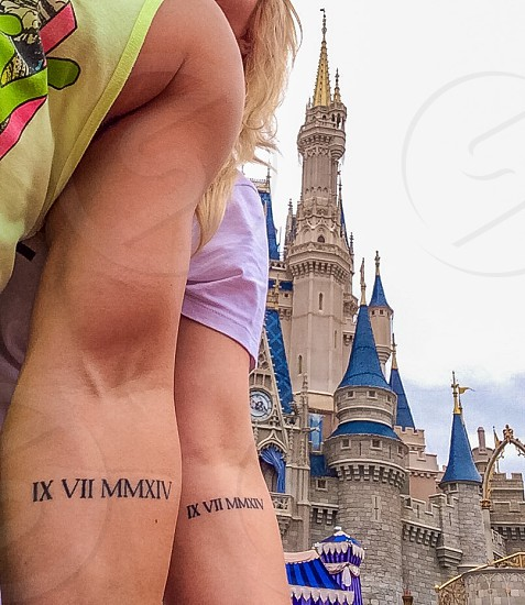 "My wife and I on our honeymoon showing off our ""wedding date"" tattoos!  photo"