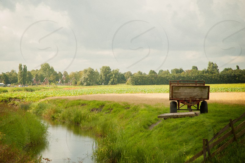 brown trailer on green grass near brown dirt road during daytime photo