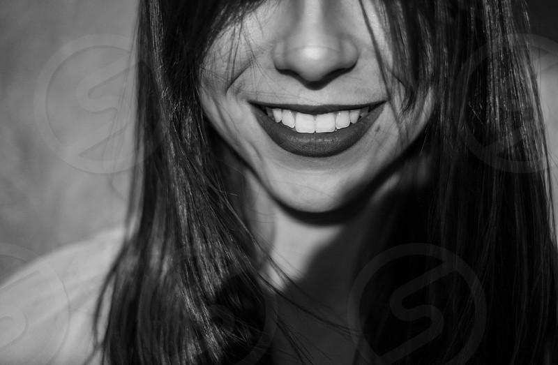 smiling brunette woman wearing lipstick grayscale photo photo