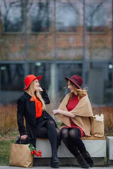 two women with hats smiling at each other photo