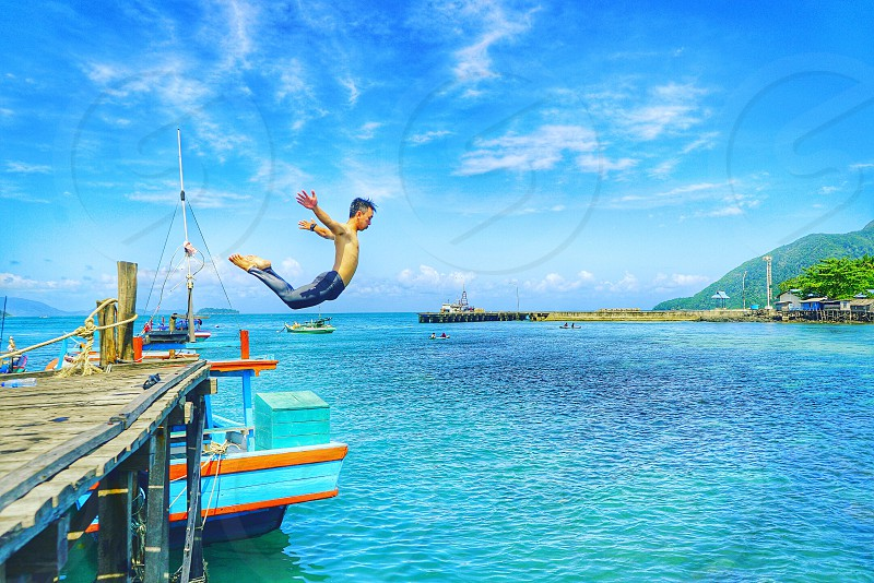 photo of a person in dock jumping on body of water during daytime photo