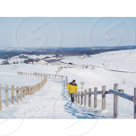 person wearing yellow and black jacket standing on snow covered ground  photo