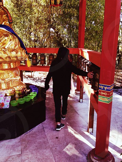 person walking through shrine near gold statue with arm out photo