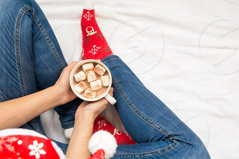 Woman taking mug with hot chocolate and marshmallow on white bed. Overhead shot. photo
