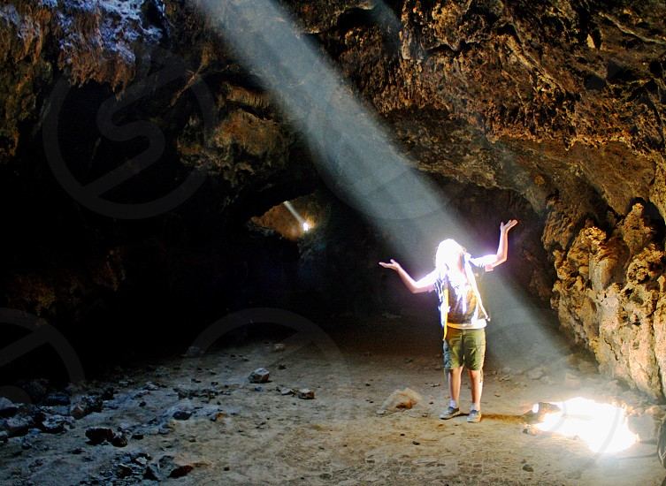 A strong beam of sunlight shoots through an opening in a cave enveloping a girl with upraised arms. photo