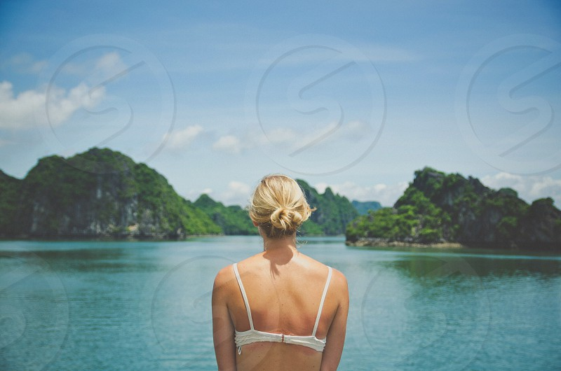 view of woman facing the green water ocean and green islands photo