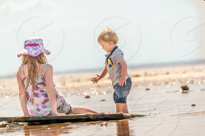 boy in gray polo shirt standing beside woman sitting on shore wearing white pink bucket hat photo