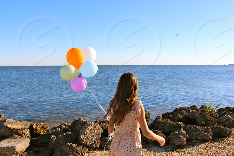 Girl holding balloons at the beach photo
