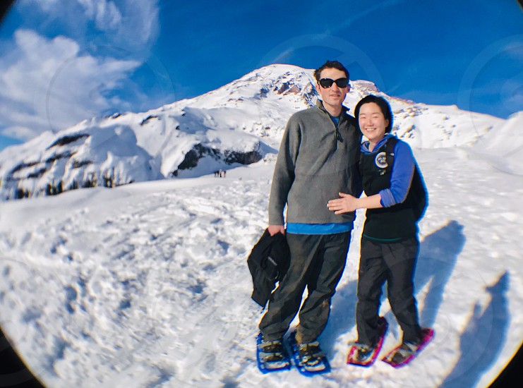 Couple snowshoeing snowshoe happy together duo sunny snow snowing mountains winter white blue sky sky  photo