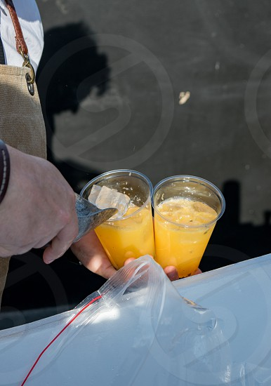 Bartender puts ice cubes into fresh beverage in plastic glasses at the bar photo